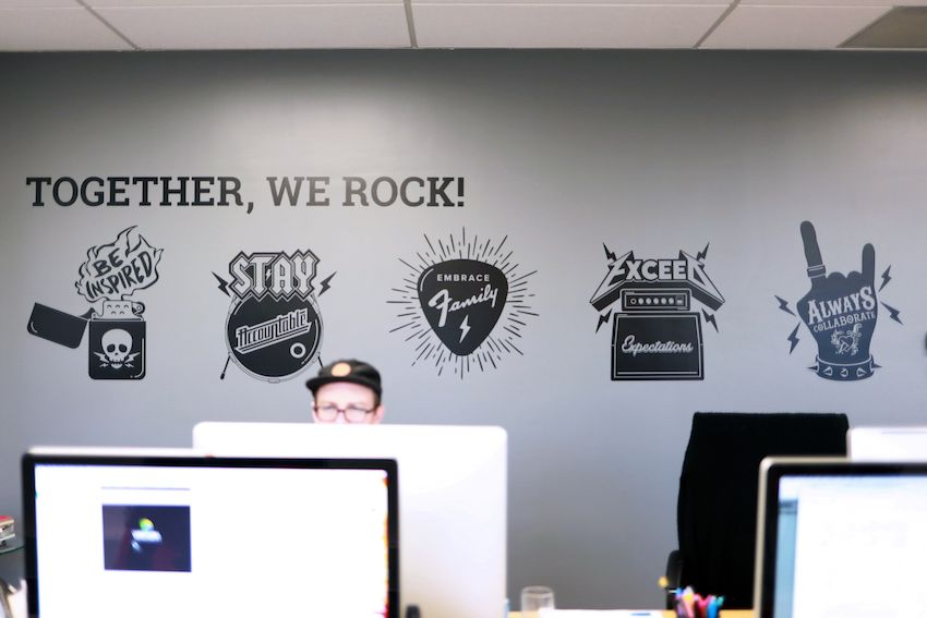 together we rock core values behind employees at computers