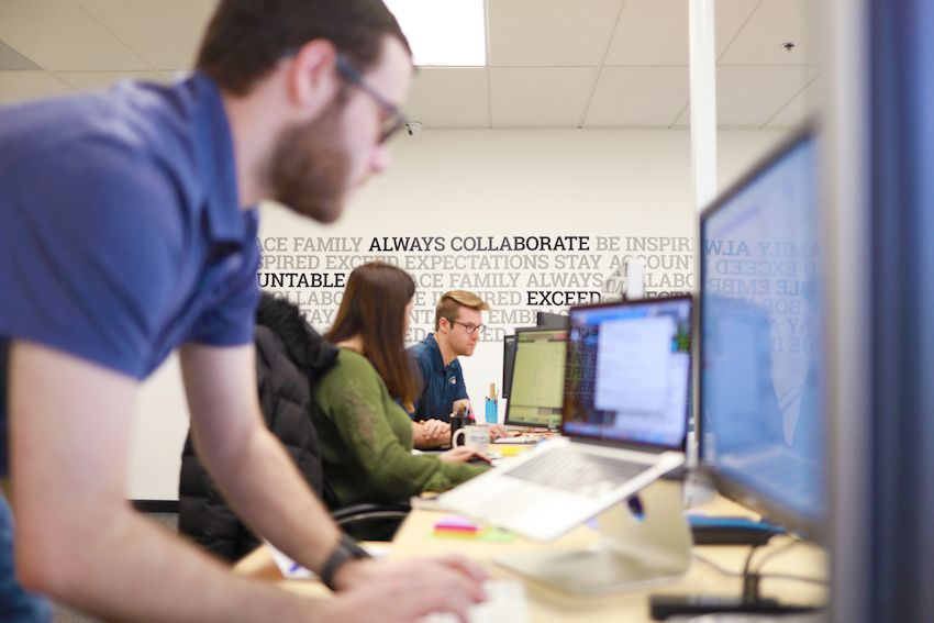 employees at desks open workspace core values on wall
