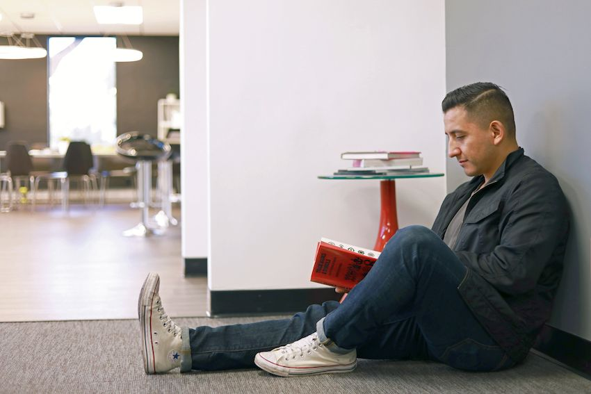 employee sitting against grey wall reading book